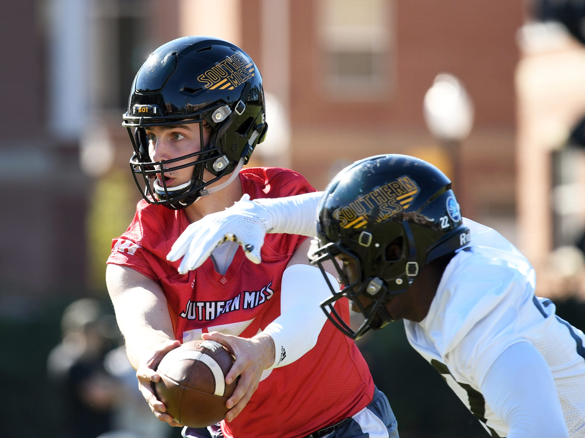 Southern Miss quarterback Jack Abraham hands the ball to running back Trivenskey Mosley during the first day of spring practice in Hattiesburg on Tuesday, March 19, 2019.