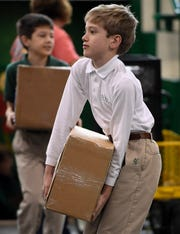 Aleks Ratley, 10 years-old, struggles with a heavy box of books as staff, students and volunteers get ready for the annual Holy Name School book sale fundraiser Wednesday, March 20, 2019.