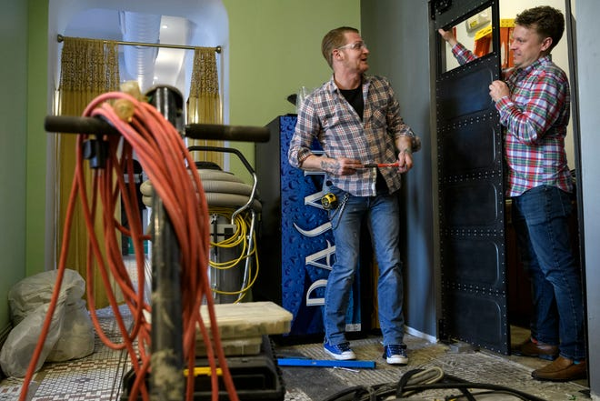Zachariah Hust, left, of Matthew's Creek Ironworks and Casey Todd, right, Hometown Roots restaurant owner,  work to install swinging doors inside Roast Coffee Bar, a new coffee shop, which will be located beside the restaurant in downtown Henderson, Ky., Thursday evening, March 14, 2019. The new coffee shop is scheduled to open at the beginning of April 2019.