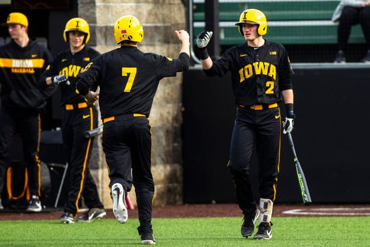 Iowa's Grant Judkins (7) bumps fists with infielder Brendan Sher (2) after scoring a run during a NCAA non conference baseball game on Tuesday, March 19, 2019, at Duane Banks Field in Iowa City, Iowa.