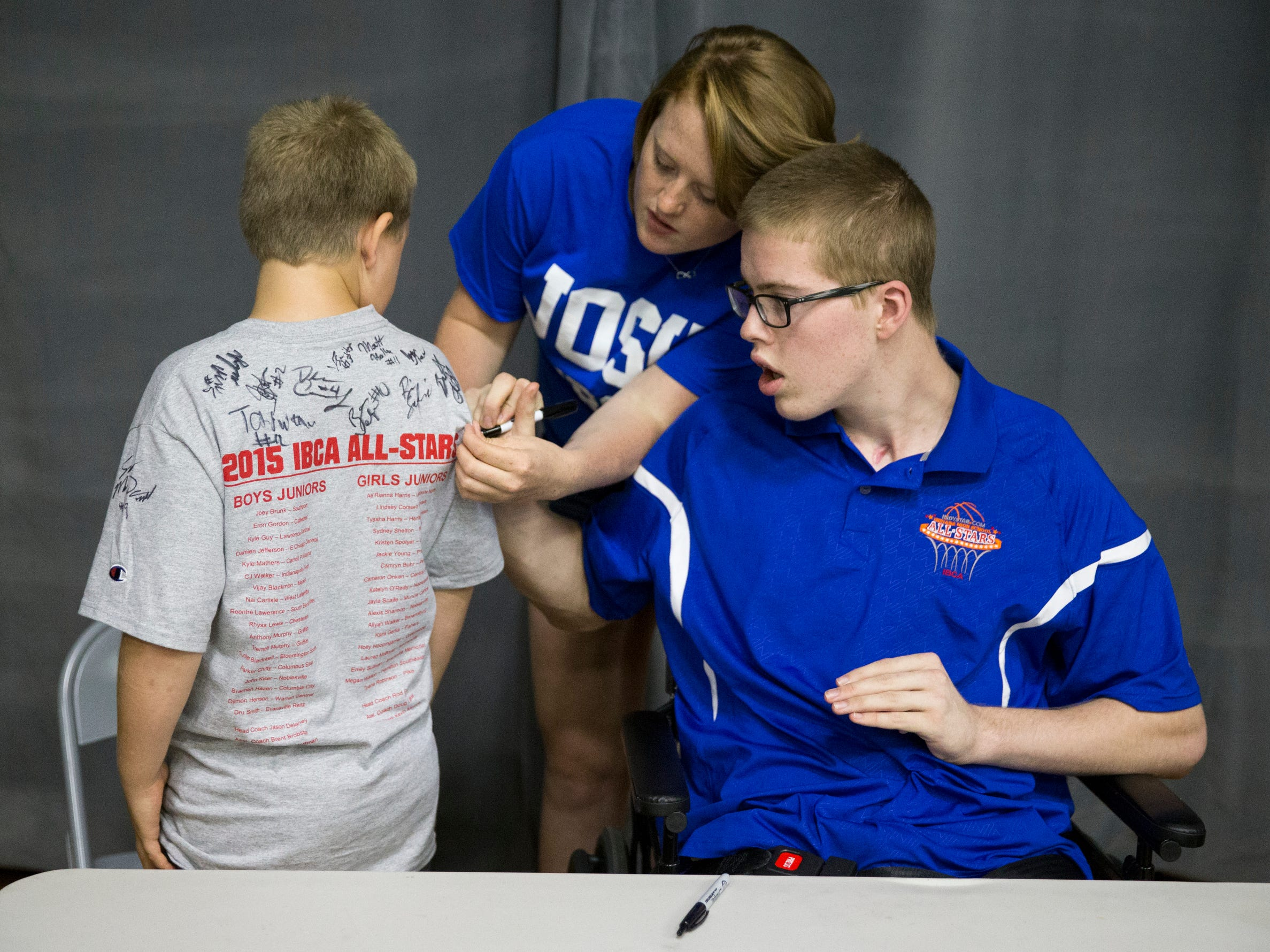 Josh Speidel, a seriously injured player for Columbus North High School, gets help from his sister Micayla Speidel, as they sign the shirt of Elix Preson, 10, Brownstown, as Speidel and other members of the Indiana Basketball All-Stars sign autographs before action against the Indiana juniors, Columbus North High School, June 10, 2015.