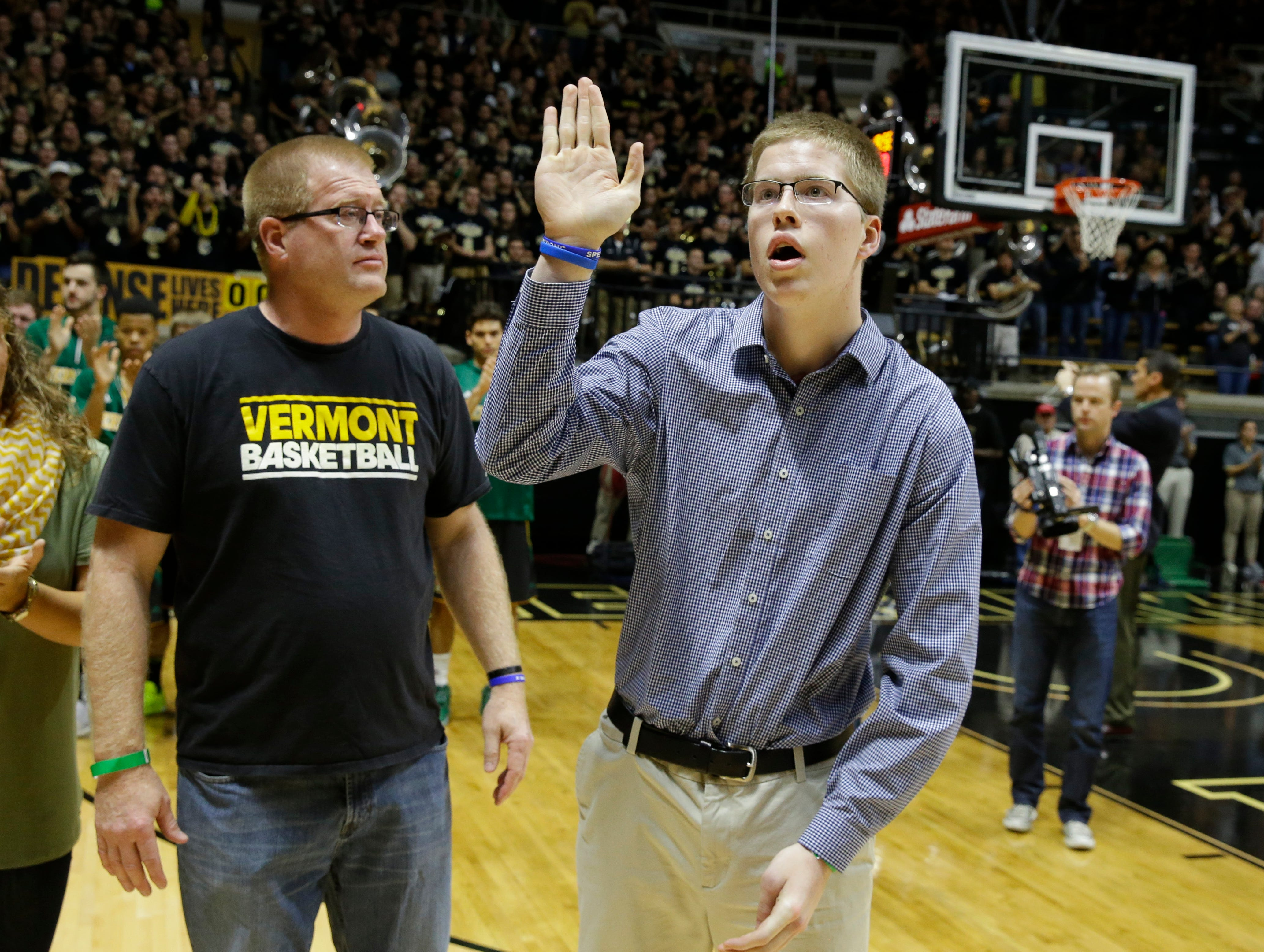 Dave Speidel, left, watches as he son Josh Speidel, right, is introduced with the Vermont players before a game against Purdue in West Lafayette, Nov. 15, 2015. Speidel is recovering from a Feb. 1 auto accident that resulted in a traumatic brain injury.