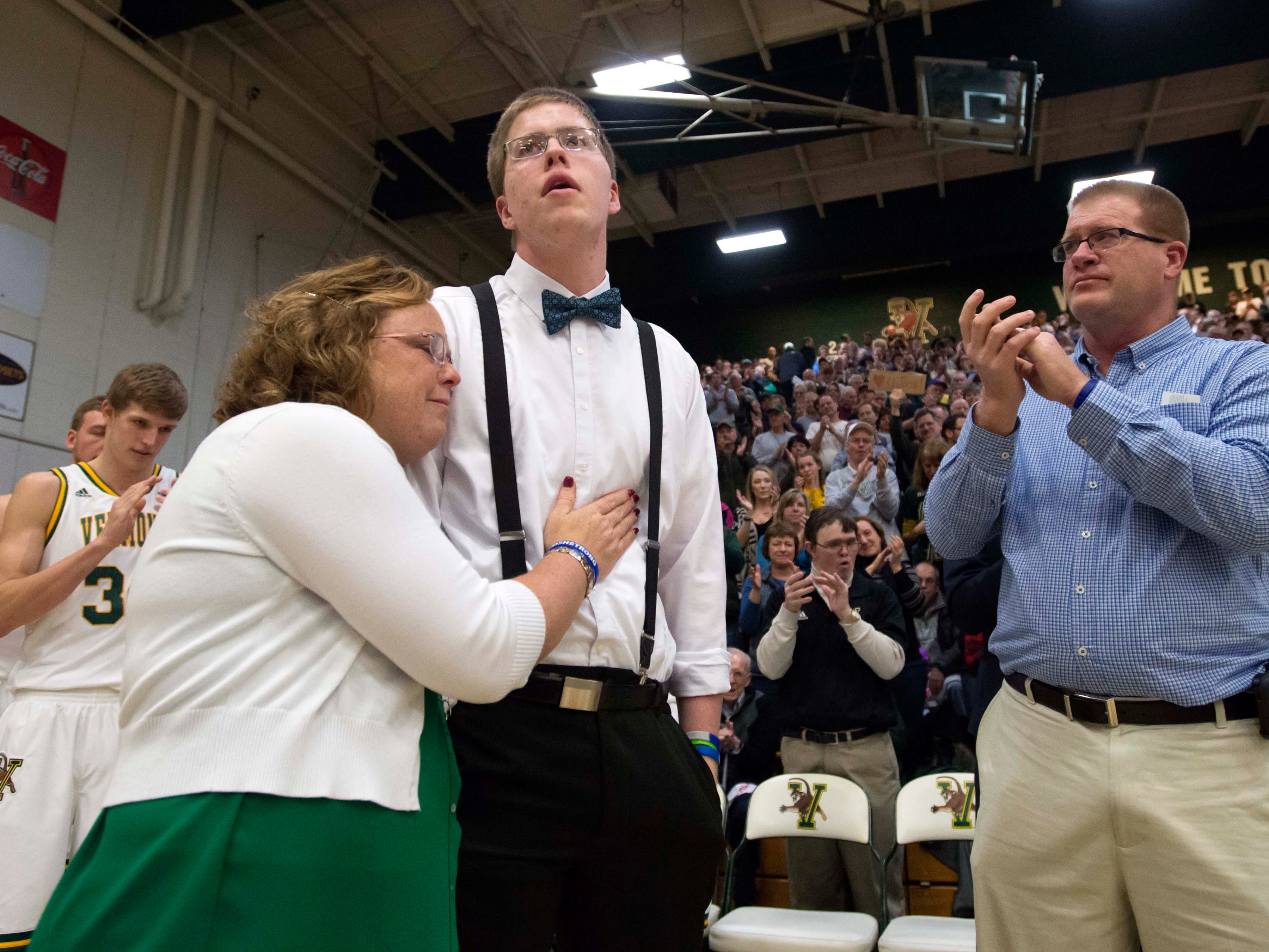 Josh Speidel gets a hug from his mother Lisa as his father Dave looks on as he is introduced before the start of the University of Vermont's game against Stony Brook's in Burlington on, January 30, 2016.