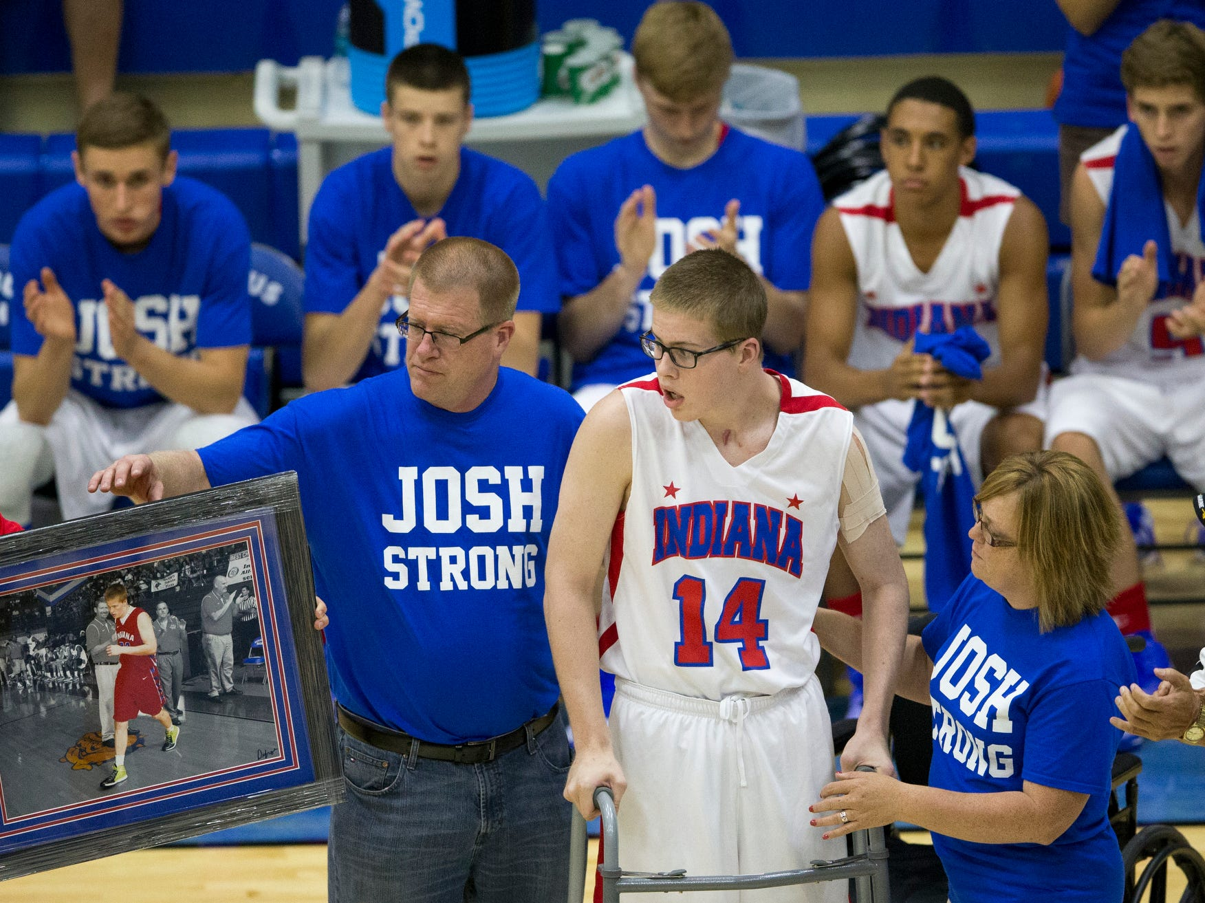 Josh Speidel, a seriously injured player for Columbus North High School, takes a few steps as he is introduced before Indiana Basketball All-Stars action against the Indiana juniors, Columbus North High School,, June 10, 2015.