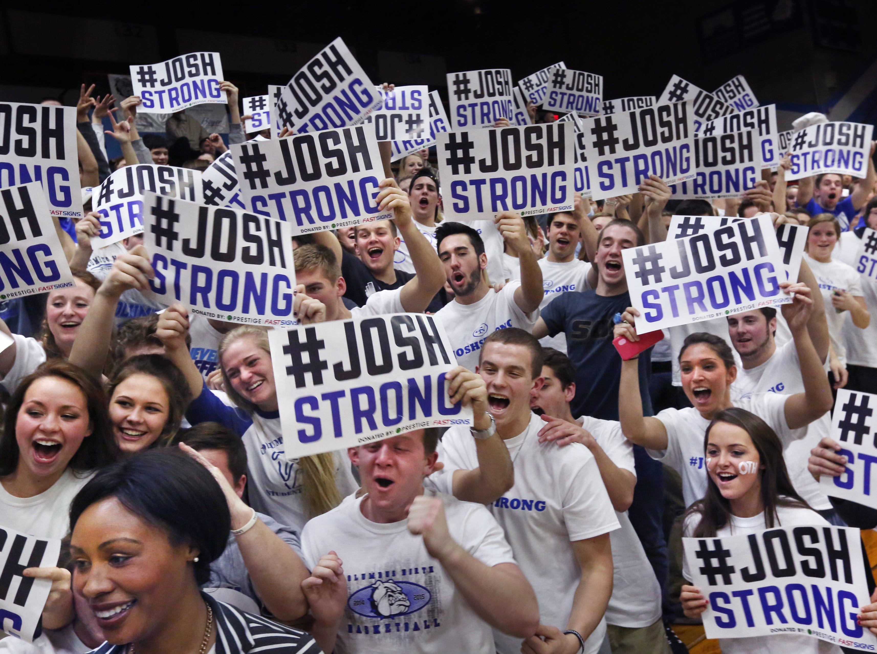 Columbus North students cheer wildly holding their #Joshstrong signs, Feb. 3, 2015. The team's star basketball player, Josh Speidel, was critically injured in a two-car accident on U.S. 31.