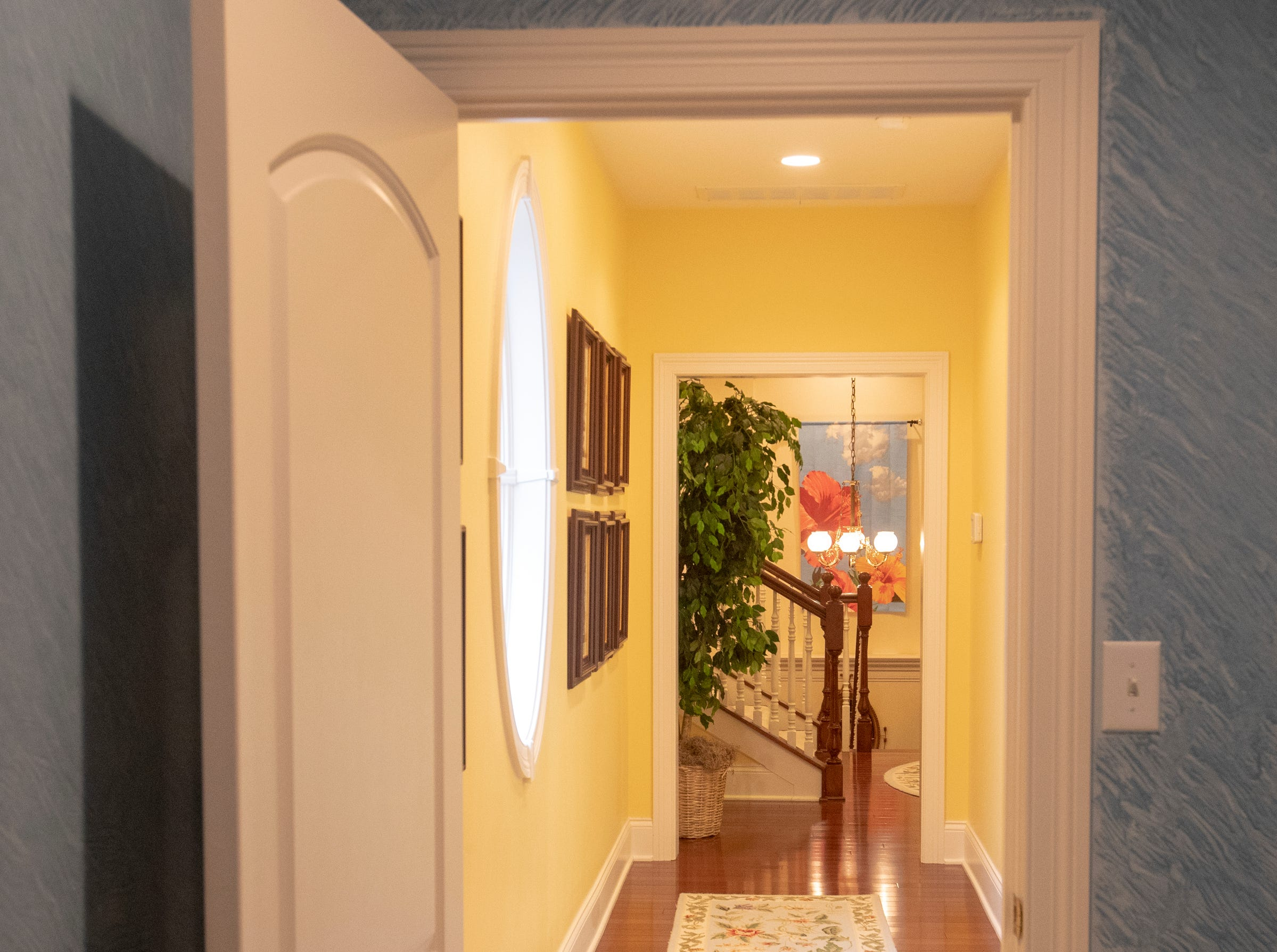 A hallway featuring natural light and hardwood floors that run throughout a thirteen-year-old Victorian home in the Village of West Clay, Carmel, March 20, 2019. The house includes 16 rooms with five bedrooms, 8,348 square feet, and is listed at $1.275 million.