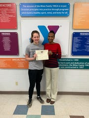 Abby Little holds the President's Volunteer Service Award that she received last year. She stands with Tymikia Glenn, the Milan YMCA CEO.