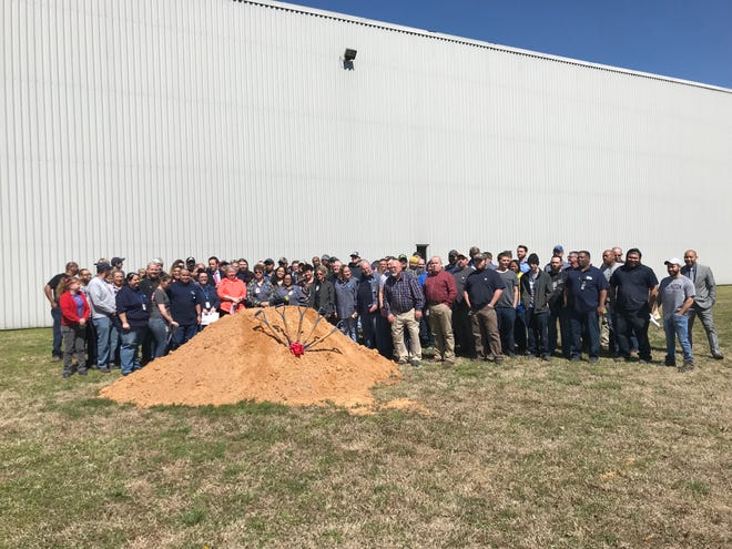 All the employees from the Jackson Bobrick Washroom Equipment manufacturing facility gather to break ground on the area where the company plans to expand on March 19 in Jackson, Tenn.