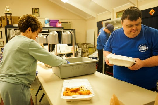 Holy Cross volunteers serve fried catfish during the Lenten season.