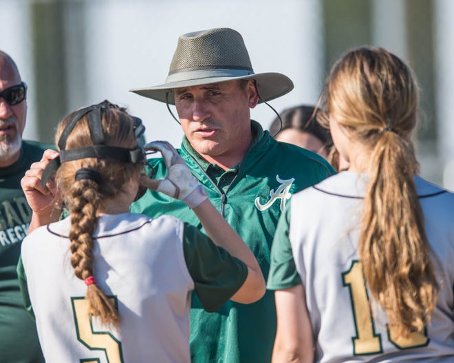 Acadiana High head softball coach Kevin Smith meets with this team during a timeout as the Acadiana Lady Rams' softball team plays host to the Comeaux Lady Spartans on Tuesday, March 19, 2019.