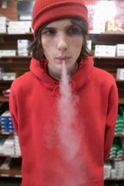 Justin Hardesty, 19, an employee at Smoker's Depot of Howell, demonstrates the exhale of an e-cigarette on Tuesday, March 19, 2019.