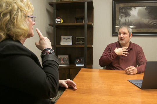 Debbie Morrison, Senior Business Developer for SignIFICANT, uses American Sign Language to speak with her husband Todd Morrison, SignIFICANT founder and president, who is deaf, in their Brighton Township office Wednesday, March 20, 2019.