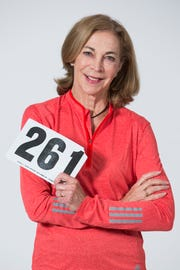 Kathrine Switzer poses in 2017 with a replica of her Boston Marathon 261 bib.