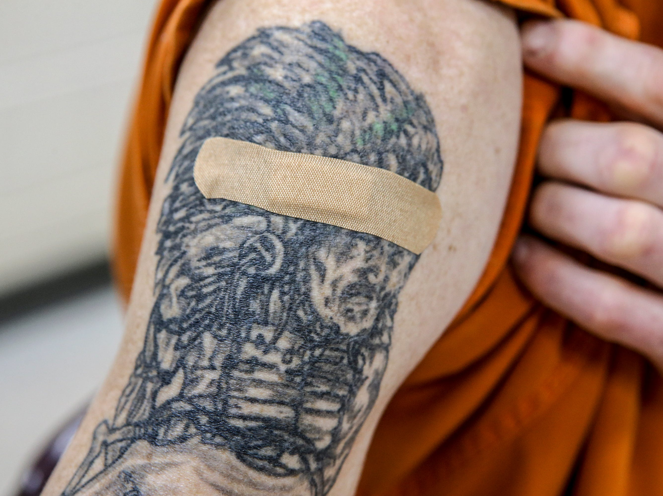A bandage is placed over the spot where a vaccination against hepatitis A was given to an inmate a the Pulaski County Detention Center by Sharon Wesley.