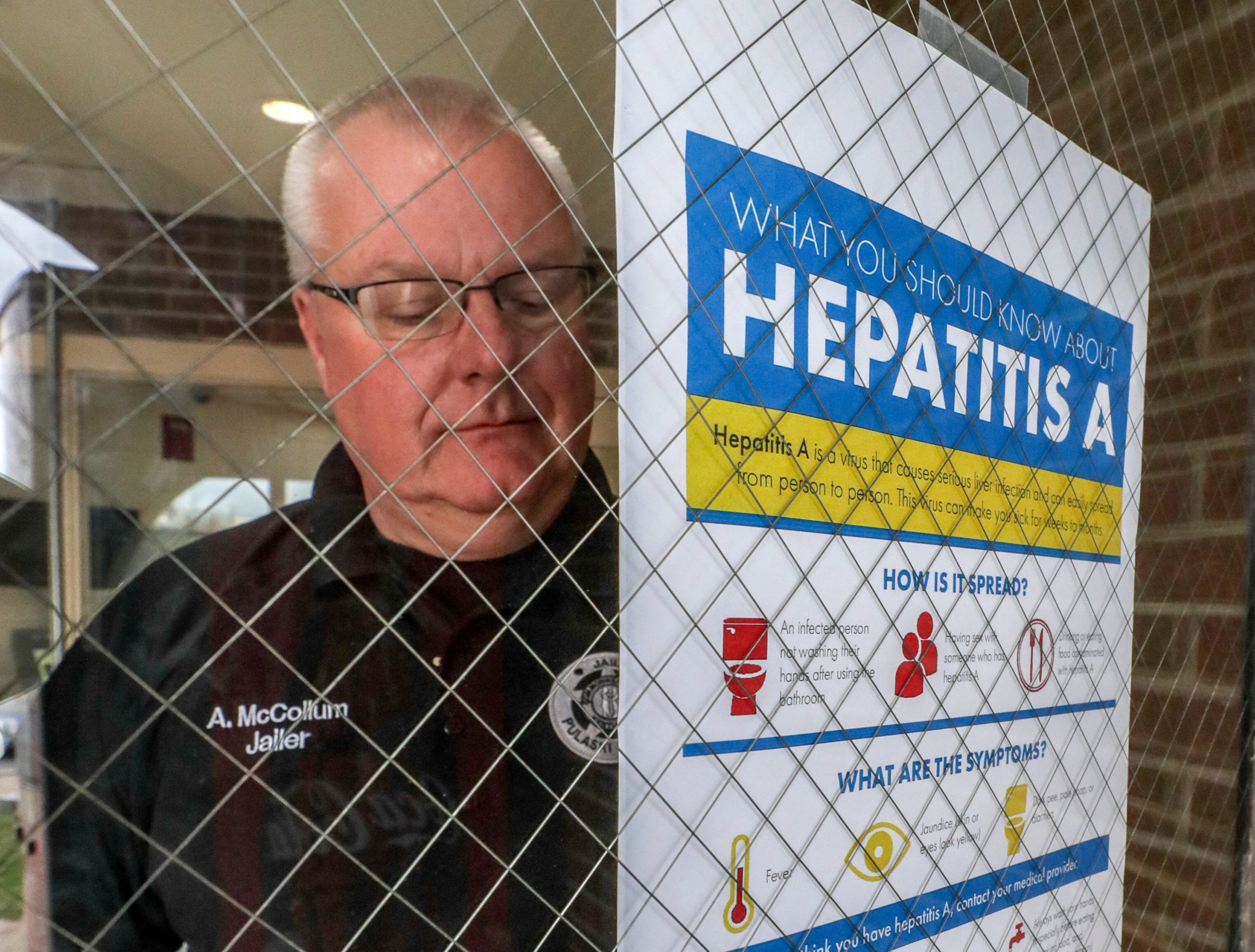 Pulaski County Detention Center Jailer Anthony McCullum looks for a place to hang a hepatitis A vaccination poster at the jail.  He has begun offering vaccinations for hepatitis in his jail after two inmates became ill.  About 90 percent of inmates opt to get vaccinated.