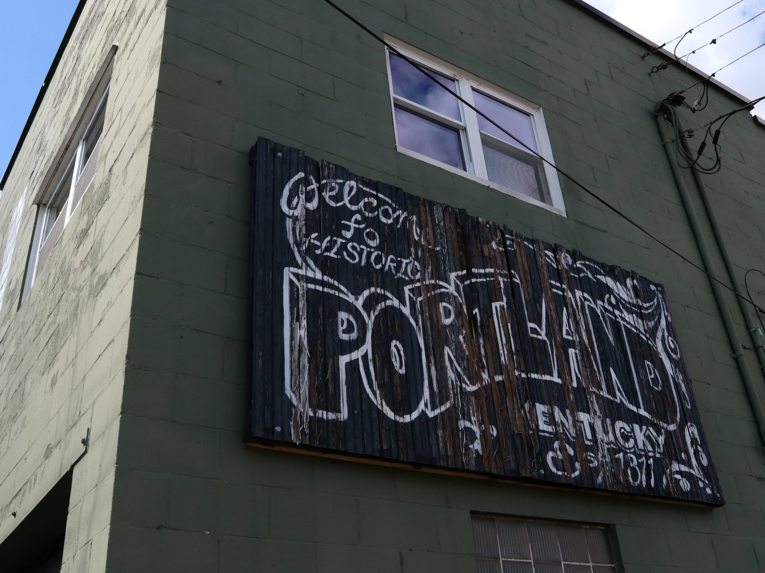 A sign welcoming people to Louisville's Portland neighborhood hangs on the wall of a building on west Main Street.