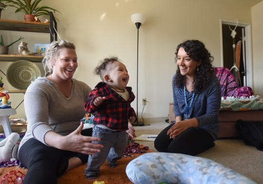 Danielle Krimmel, left, and 6-month-old son Mykah play with Kristin Arnold, an RN with the Ingham County Health Department, Tuesday, March 19, 2019, during a home visit at Krimmel's home in Delta Township.
