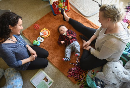 Danielle Krimmel, right, and 6-month-old son Myka with Kristin Arnold, an RN with the Ingham County Health Department, Tuesday, March 19, 2019, during a home visit at Krimmel's home in Delta Township.