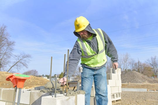 Josh Holland, of Ashland, lays mortar Wednesday morning before setting block that will form an elevator shaft at the new UH Samaritan Richland Health Center location in Mansfield.