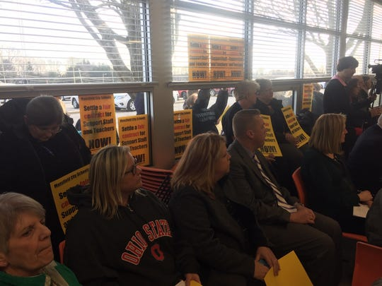 Some people even stood outside the meeting room, waving their signs in the windows.