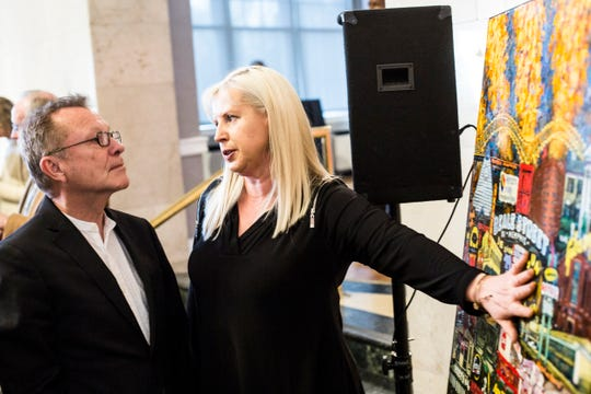 March 19, 2019 - Artist Evelina Dillon, right, talks with Barry Alan Yoakum of Archimania during a party to unveil Dillon's artwork as the 2019 Memphis in May Festival fine arts poster at the Pink Palace Museum.