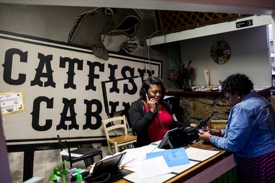 Shayla Carson, general manager at Catfish Cabin, takes a call while working during the lunch shift March 19, 2019.