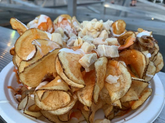 A mound of potato chips topped with buffalo sauce, ranch dressing and chicken from the Collier County Fair.
