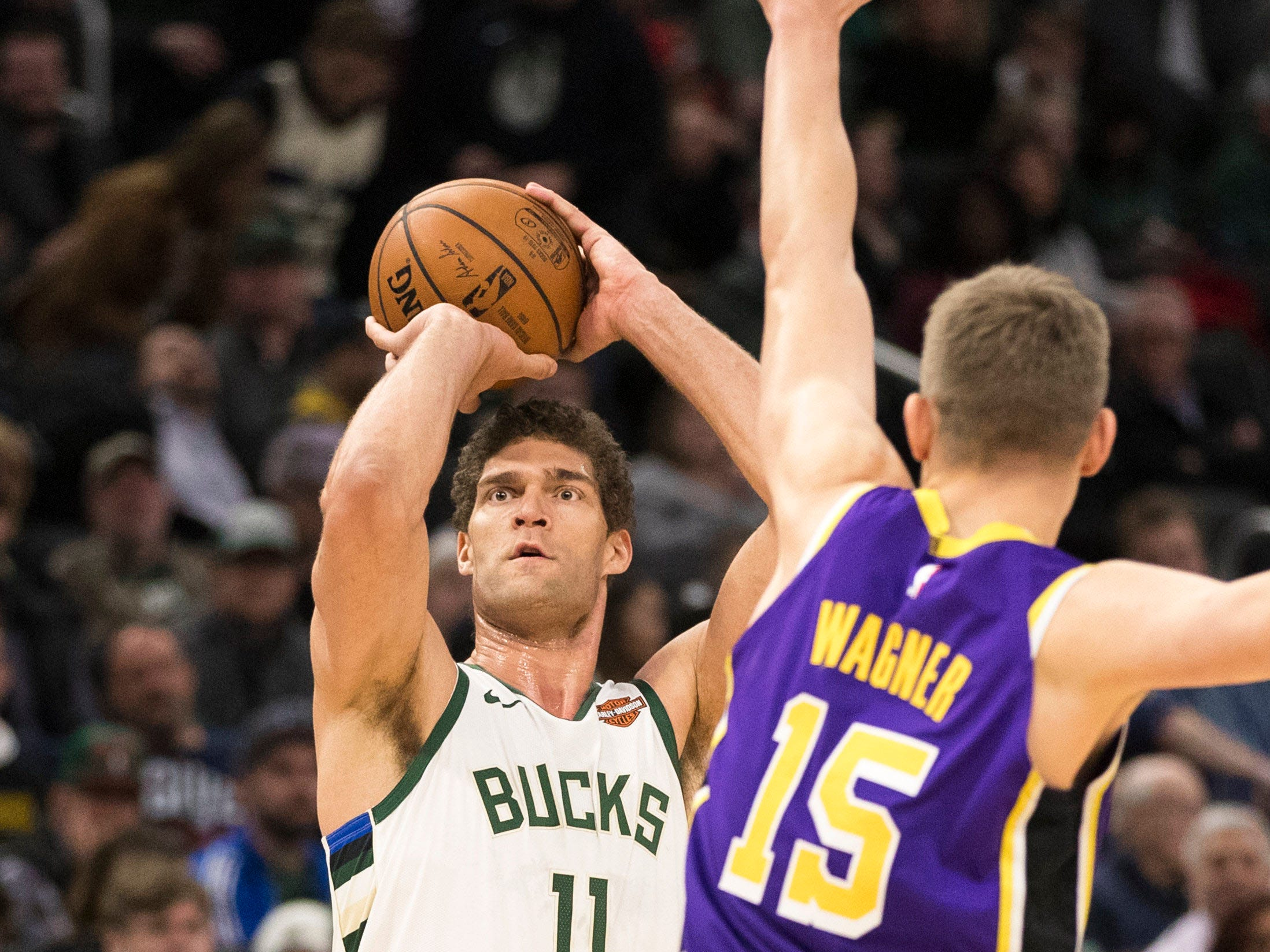 Bucks center Brook Lopez  shoots the ball over Moritz Wagner. Lopez finished with 28 points.
