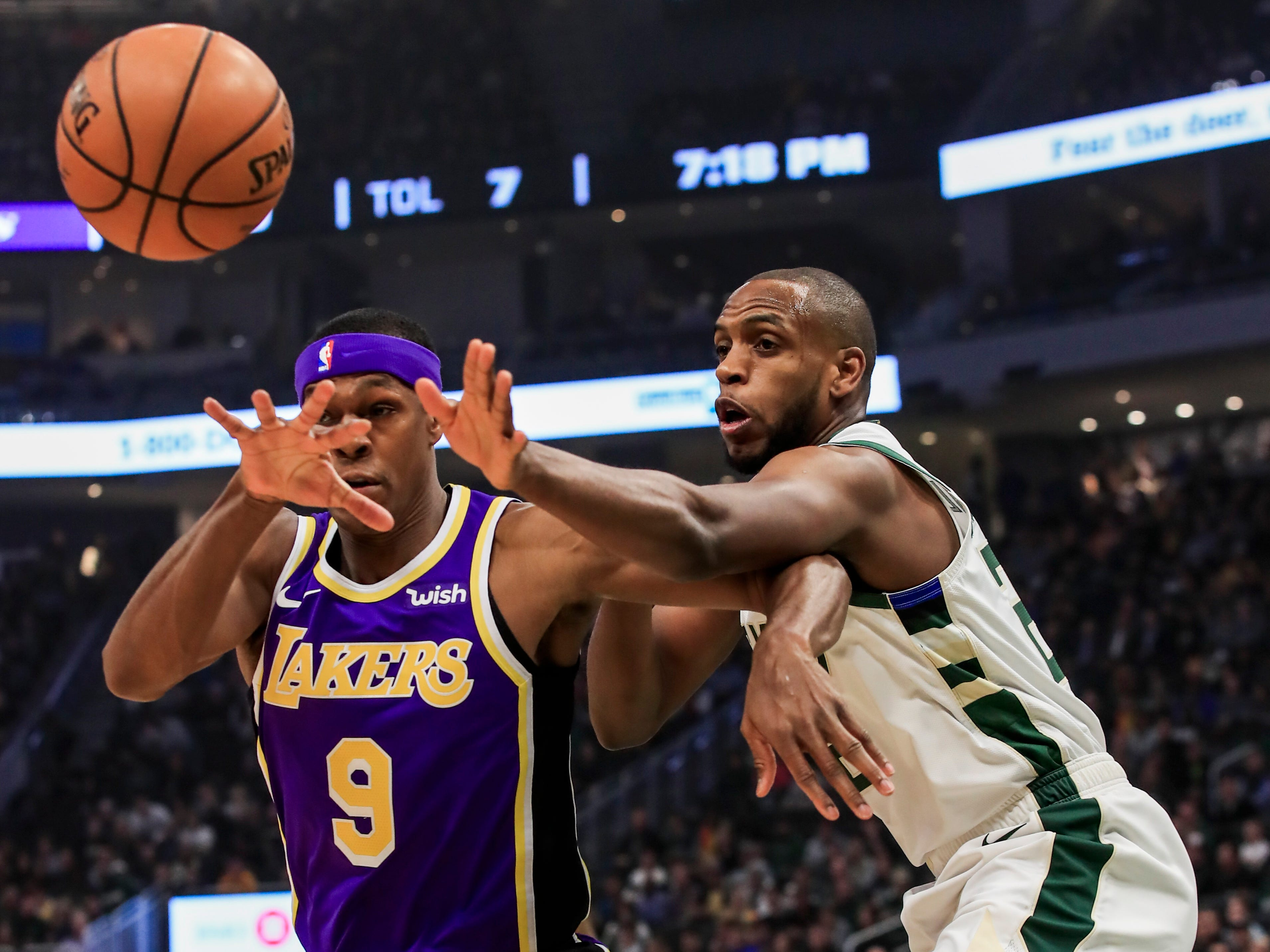 Lakers guard Rajon Rondo and e Bucks forward Khris Middleton watch the ball go out of bounds.