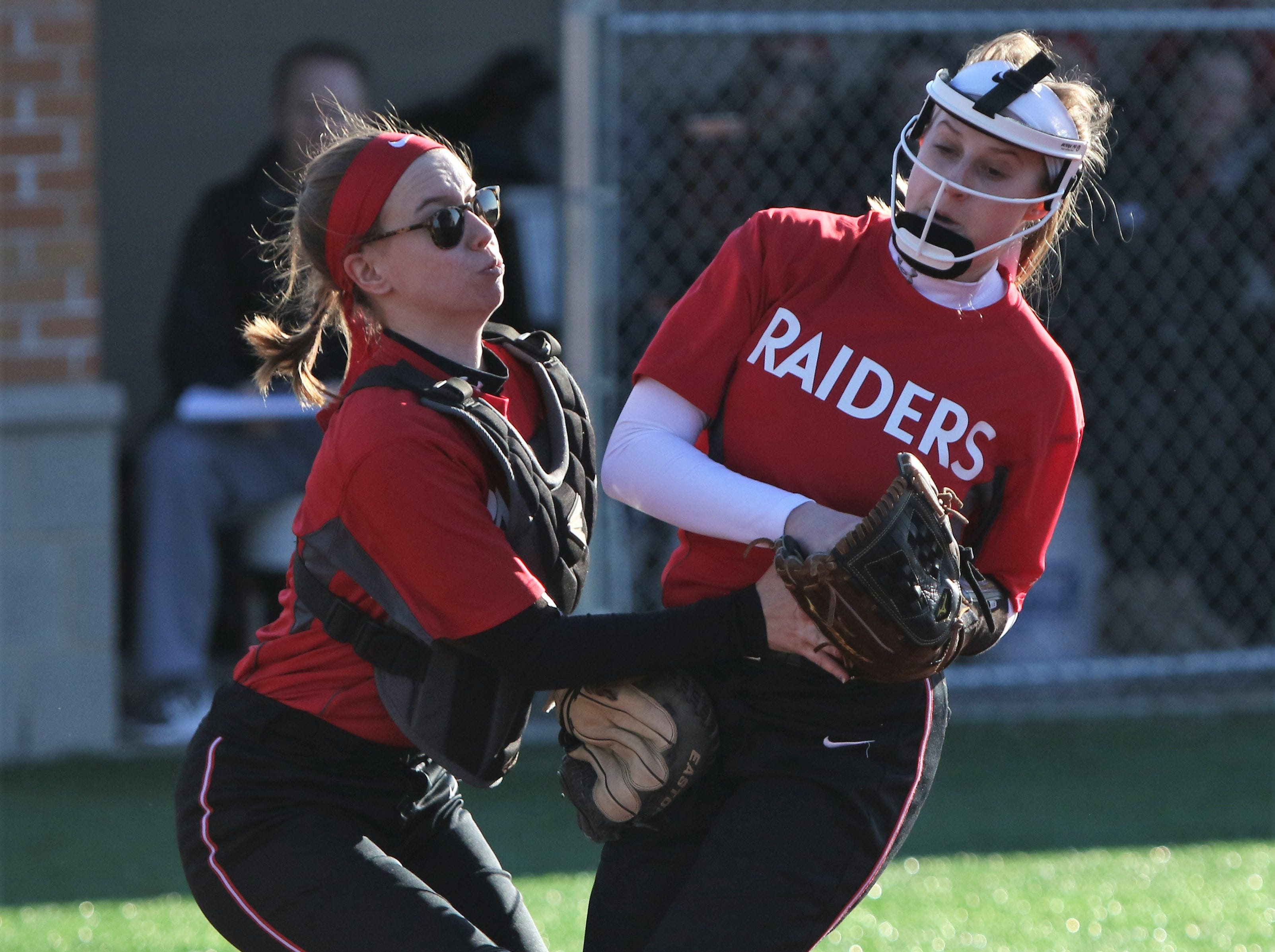 Wauwatosa East pitcher Stasia Raebel (right) nearly collides with catcher Kenzie Miller as she makes a catch against Catholic Memorial on March 19, 2019.