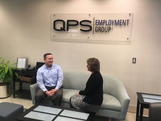 John Boettcher, workers' compensation manager for QPS Employment Group, chats with Cheryl Datka, executive administrative manager, at the  Brookfield office of QPS. The company  has been honored as a Top Workplace for 10 consecutive years.