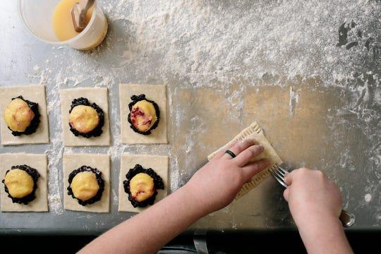 Allison forms blueberry lemon curd hand pies, a customer favorite.