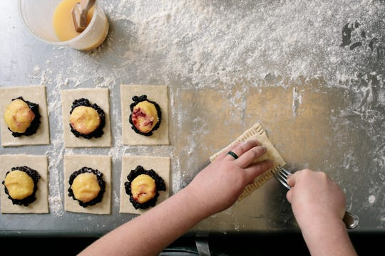 Allison forms blueberry lemon curd hand pies, a customer favorite.