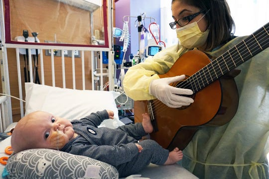 "Christina Sifnaios, a music therapist at Children's Hospital of Wisconsin, plays an amended version of Tom Petty's ""Free Fallin'"" for 7-month-old Billy McGrath during his long stay at the hospital. Billy needed a bone marrow transplant and had a tough medical journey, but Tom Petty's music cheered him up."