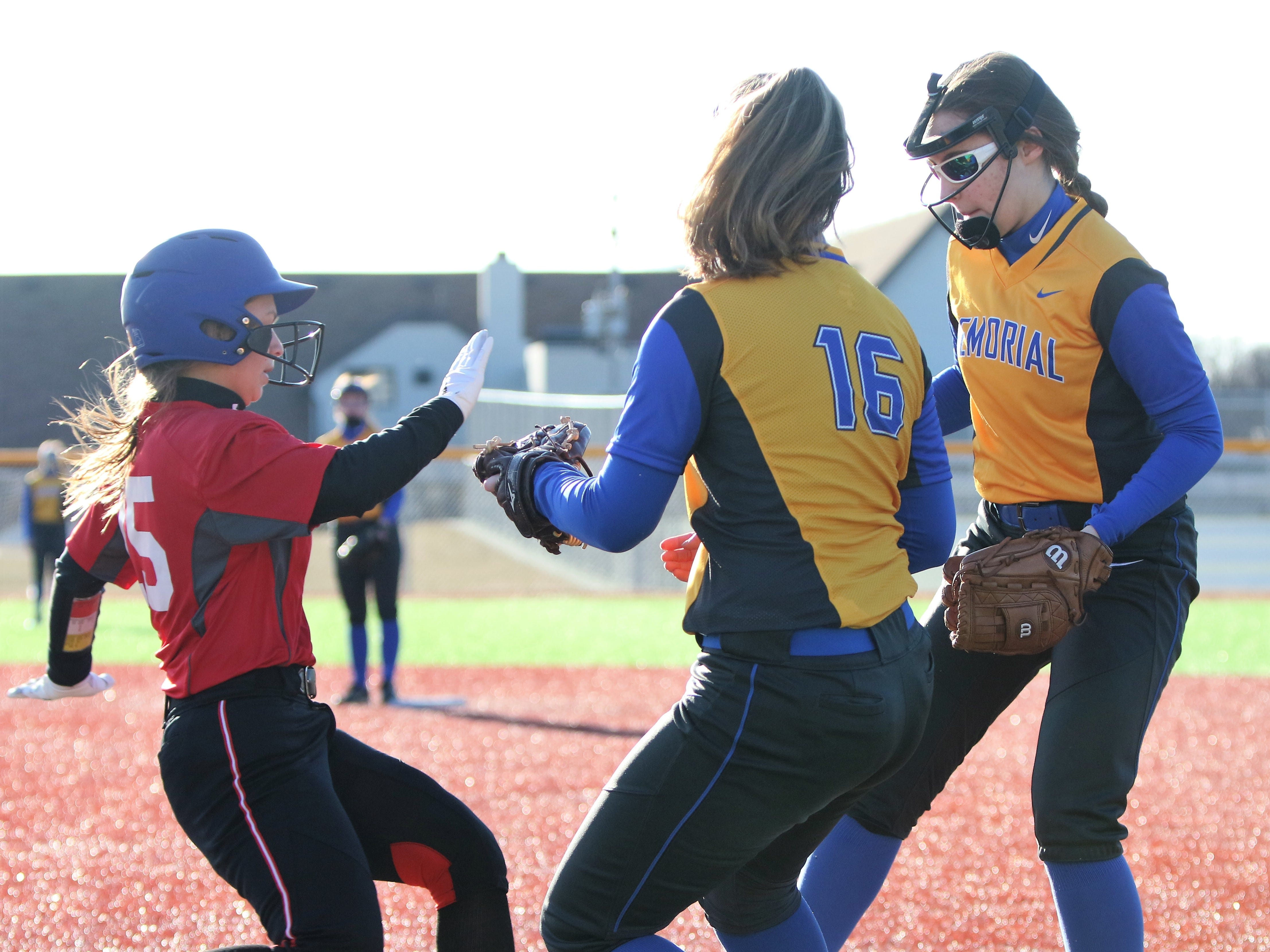 Wauwatosa East sophomore Bella Simmons (left) attempts to avoid a pair of Catholic Memorial players at first base during a game on March 19, 2019