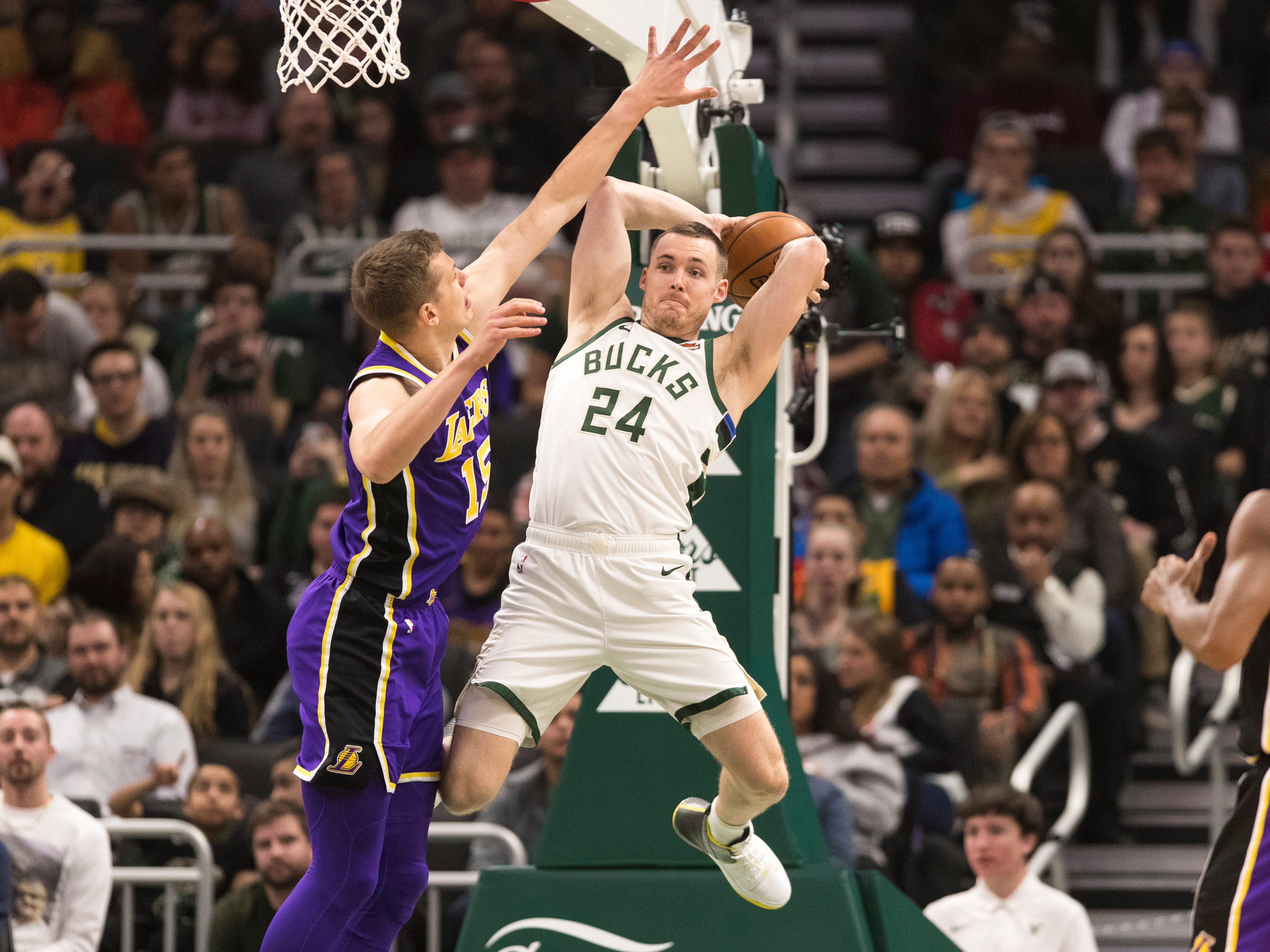 Bucks guard Pat Connaughton passes the ball under pressure from Lakers center Moritz Wagner on Tuseday night.