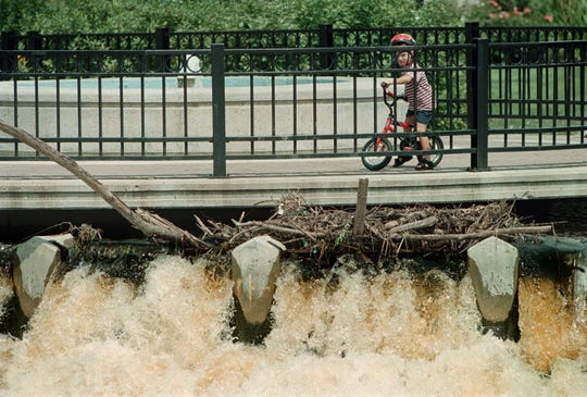 Andy Hoisington, 5, of Milwaukee, stops his bike and looks at the high volume of water rushing over the Barstow St. dam as he visits the Fox Riverwalk in Waukesha in this file photo.