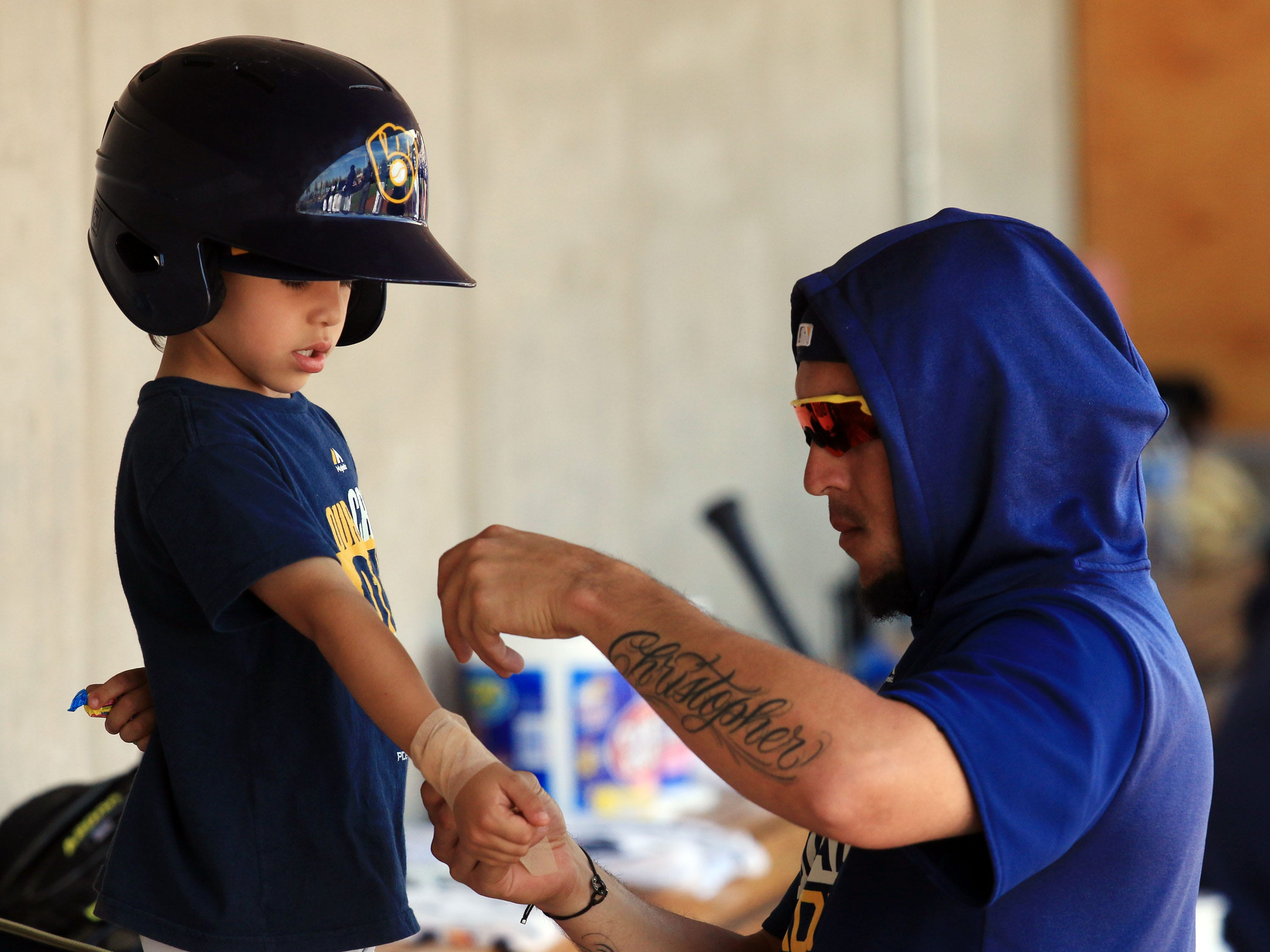 """Milwaukee Brewers Hernan Perez gives his son Christopher a """"big league"""" wrap on his wrist on March 19, 2019."""