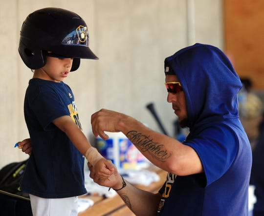 "Milwaukee Brewers Hernan Perez gives his son Christopher a ""big league"" wrap on his wrist on March 19, 2019."