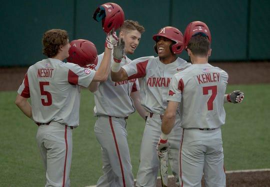 Arkansas outfielder Christian Franklin (25) celebrates a grand slam with infielder Jacob Nesbit (5) during an NCAA college baseball game against Texas on Tuesday in Austin, Texas.