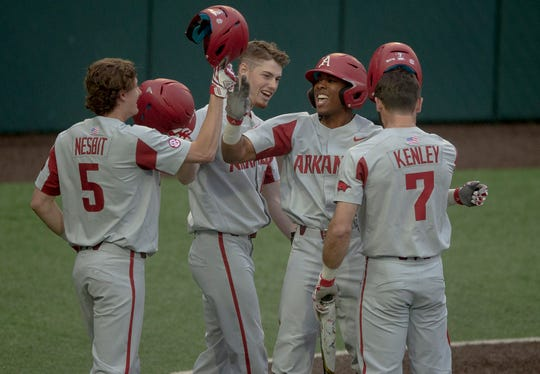 Arkansas outfielder Christian Franklin (25) celebrates a grand slam with infielder Jacob Nesbit (5) during an NCAA college baseball game against Texas on Tuesday in Austin, Texas.