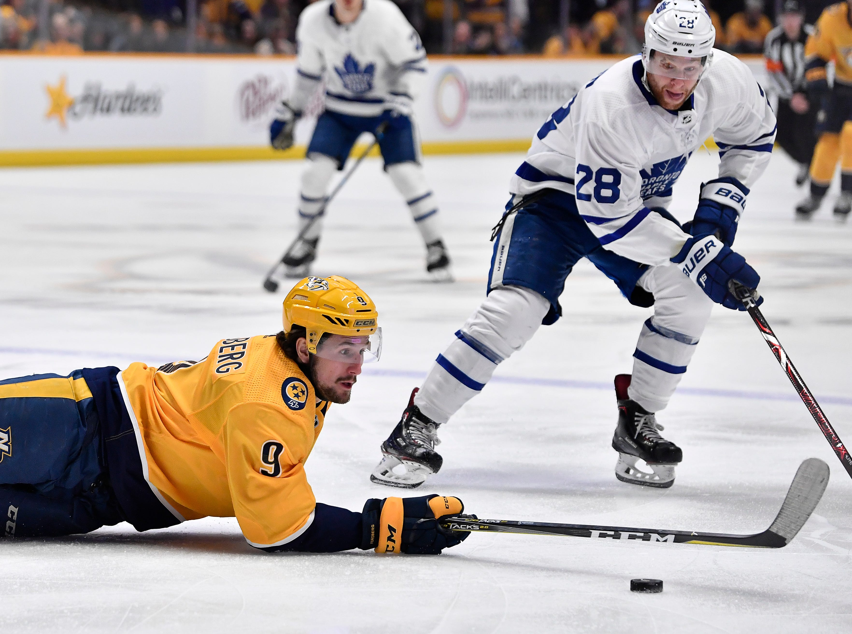 Predators left wing Filip Forsberg (9) falls to the ice as he reaches for a puck past Maple Leafs right wing Connor Brown (28) during the first period at Bridgestone Arena Tuesday, March 19, 2019 in Nashville, Tenn.