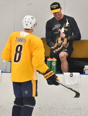 Predators goaltender Pekka Rinne shows off his puppy Pabla to center Kyle Turris (8) as he visits practice at Centennial Sportsplex Wednesday, March 20, 2019 in Nashville, Tenn.