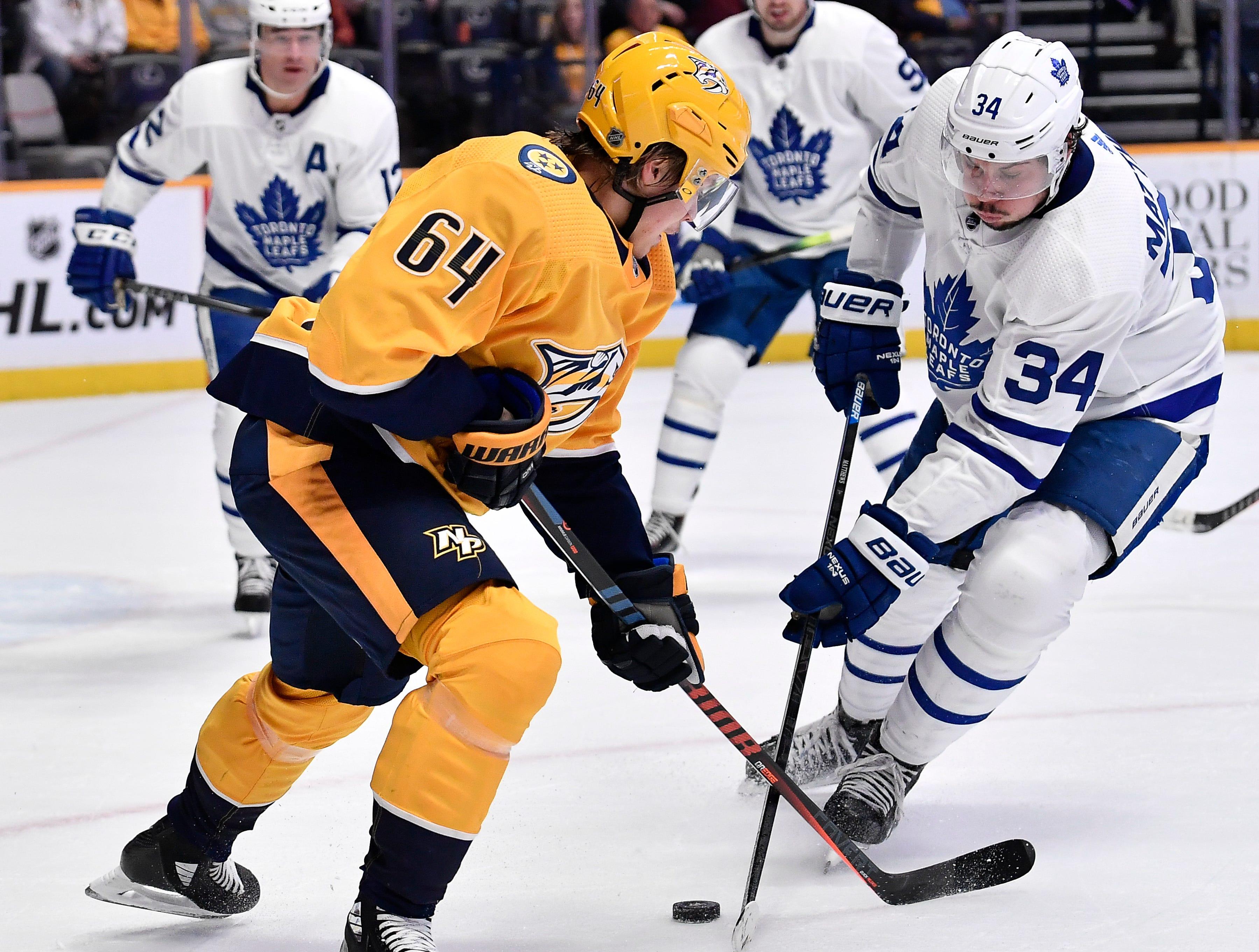 Predators center Mikael Granlund (64) fights Maple Leafs center Auston Matthews (34) for the puck during the first period at Bridgestone Arena Tuesday, March 19, 2019 in Nashville, Tenn.