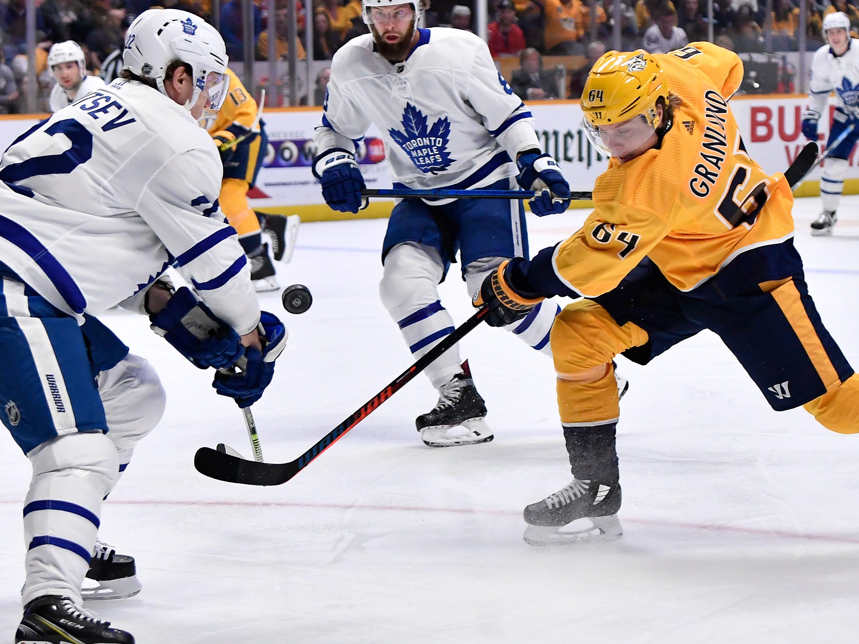 Predators center Mikael Granlund (64) tries to shot past Maple Leafs defenseman Nikita Zaitsev (22) during the first period at Bridgestone Arena Tuesday, March 19, 2019 in Nashville, Tenn.