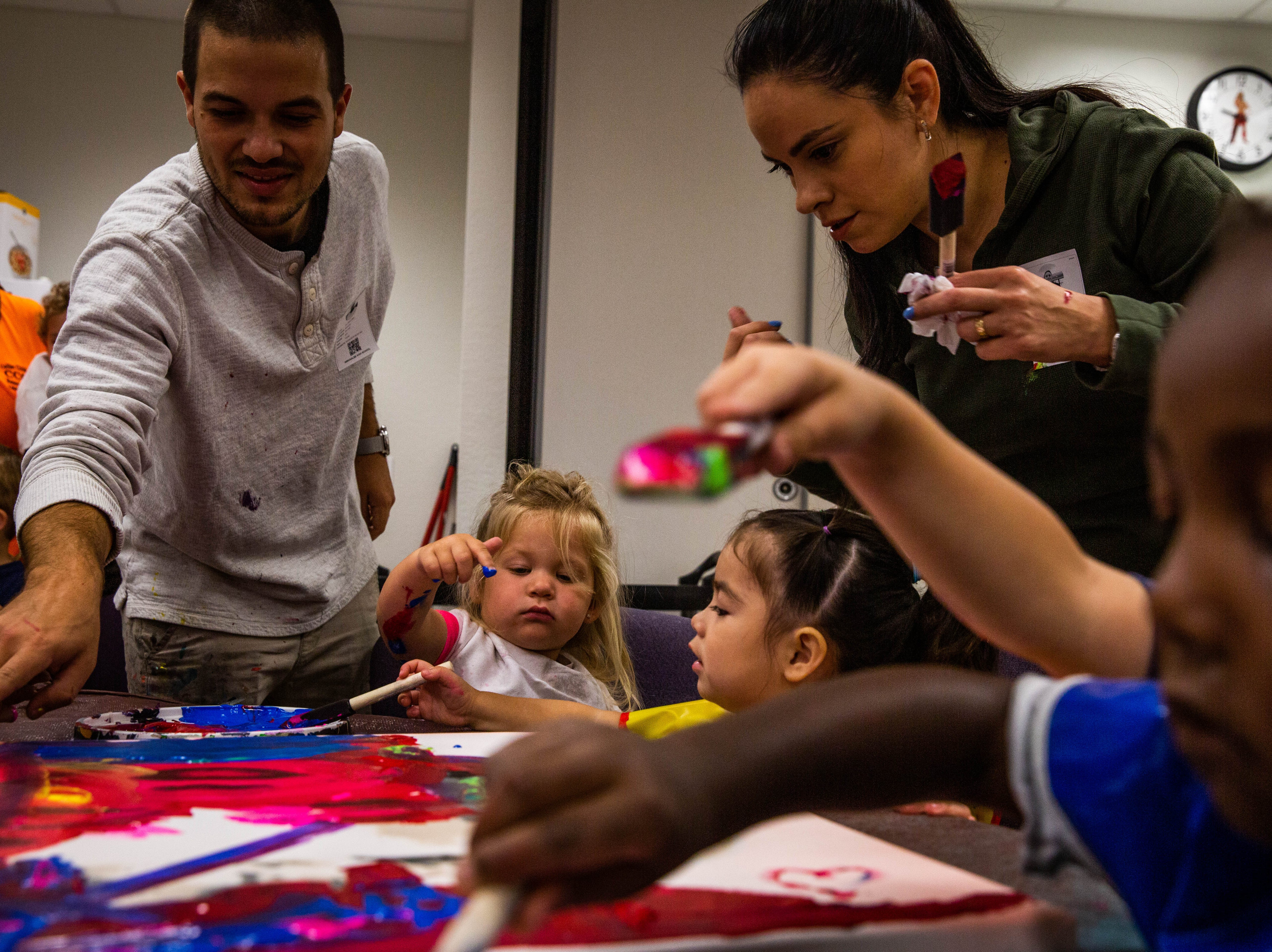 Marcus and Beatriz Zotter create art with children at A Step Up, a Collier Child Care Resources Early Childhood Development Center at Immokalee High School on March 20, 2019. The process they used with the children was inspired by street art.
