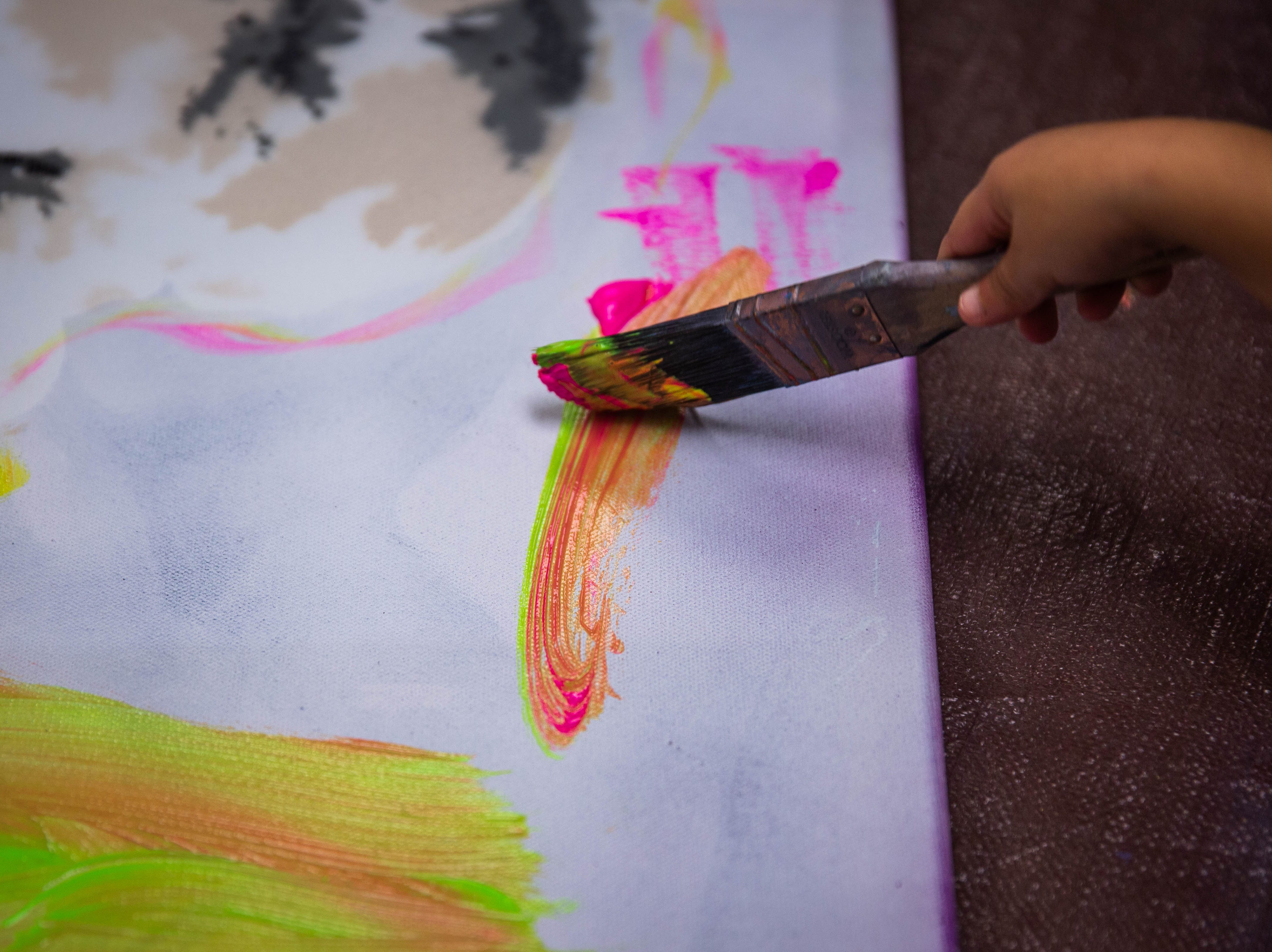 A child holds a brush while painting with Marcus and Beatriz Zotter at A Step Up at Immokalee High School on March 20, 2019. The work made by the children will be part of the Big Impressions By Little Artists gala next week.