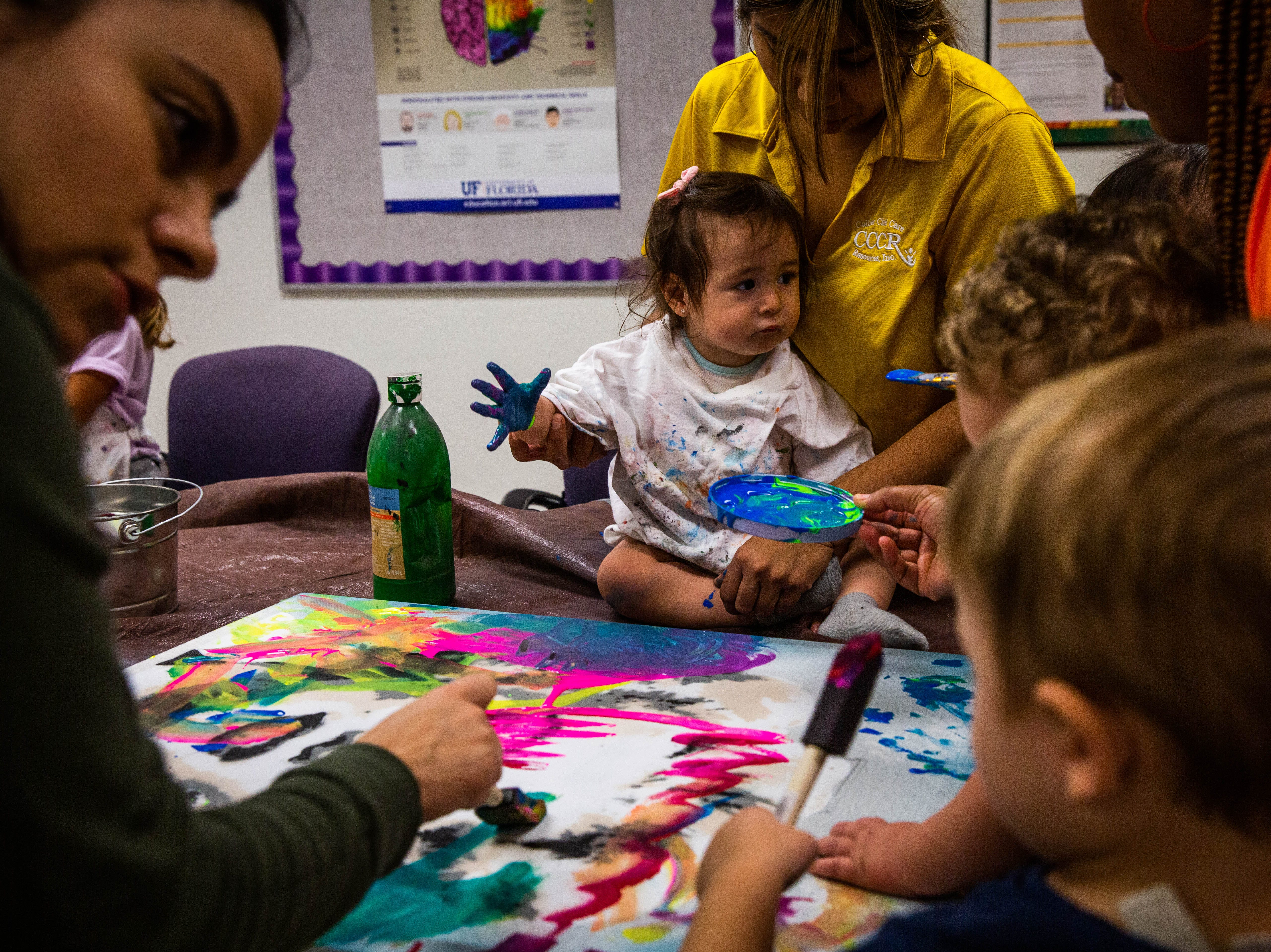 Children in A Step Up, a Collier Child Care Resources Early Childhood Development Center, create art with local artists Marcus and Beatriz Zotter at Immokalee High School on March 20, 2019. The children used paint, both on brushes as well as with their hands, to decorate canvases.