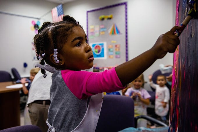 Asia Jean paints on a canvas at A Step Up, a Collier Child Care Resources Early Childhood Development Center at Immokalee High School on March 20, 2019. For the third year, local artists Marcus and Beatriz Zotter worked with the organization to create art with the children there.
