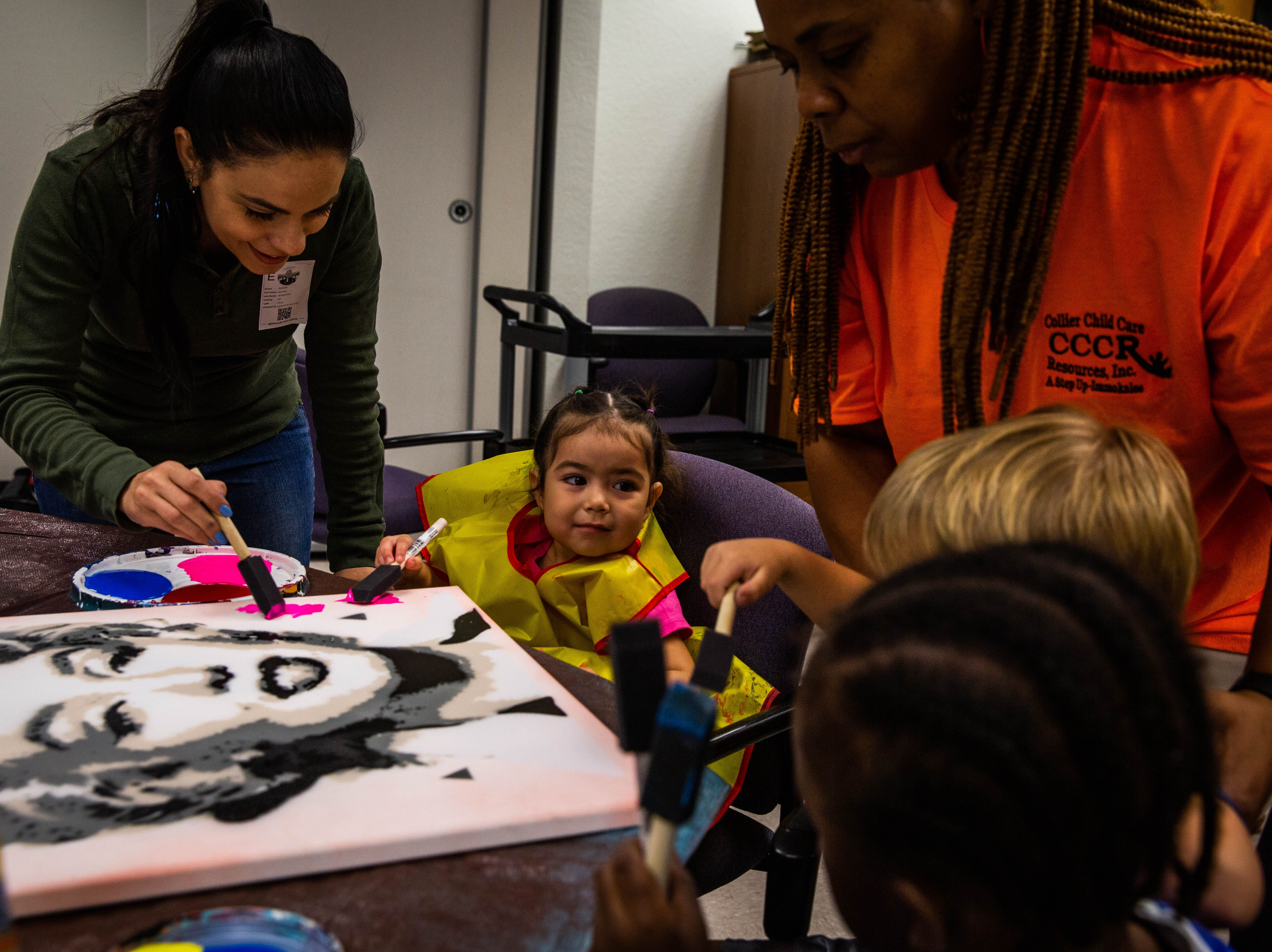 Beatriz Zotter, left, helps children at A Step Up paint on a canvas at Immokalee High School on March 20, 2019.